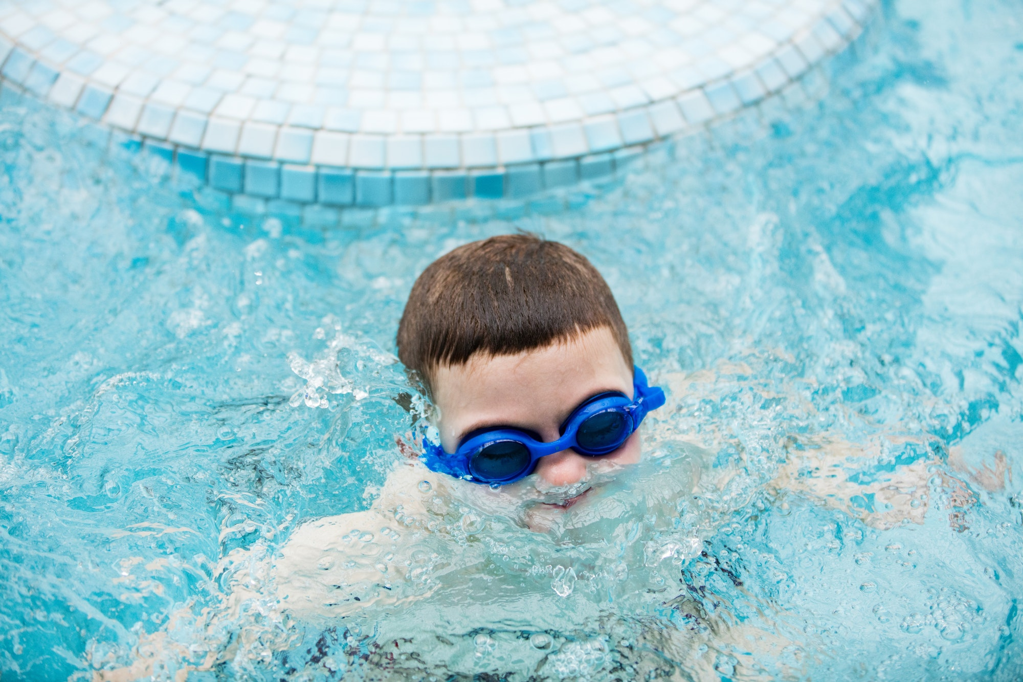 Kid in a swimming pool surfacing out of water